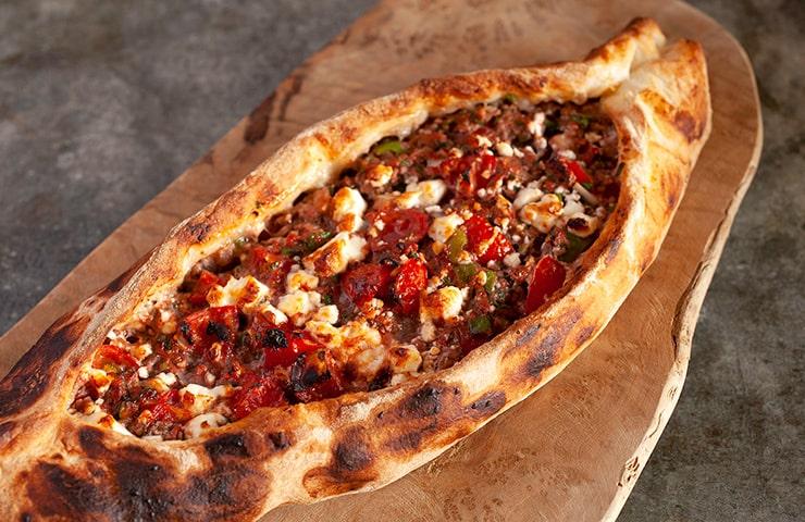 ピデ<br>船の形に焼き上げるトルコ料理「ピデ」は、フランスパンのような食感が楽しめるピザ風の惣菜パンです。